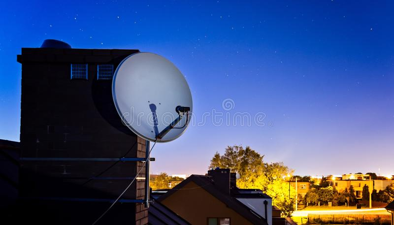 Satellite dish antenna mounted on the roof of the house. At night stock photography
