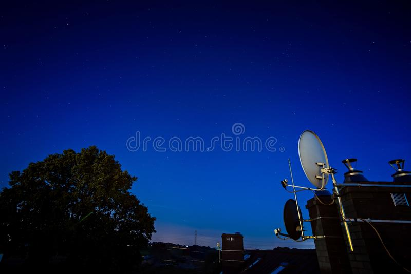 Satellite dish antenna mounted on the roof of the house. At night royalty free stock photos