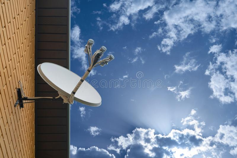 Satellite dish antenna mounted on the wall of a private house on blue sky background. Satellite dish antenna mounted on the wall of private house on blue sky royalty free stock photo