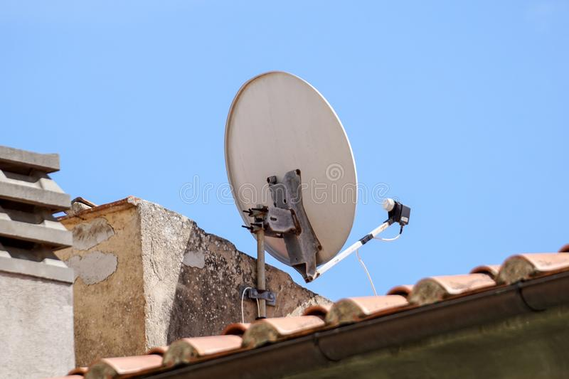 Satellite dish antenna mounted on the wall of a private house on blue sky background.  royalty free stock photos