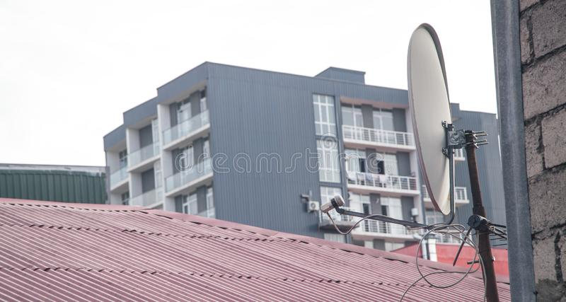 Satellite dish antenna mounted on the wall of a private house stock photography