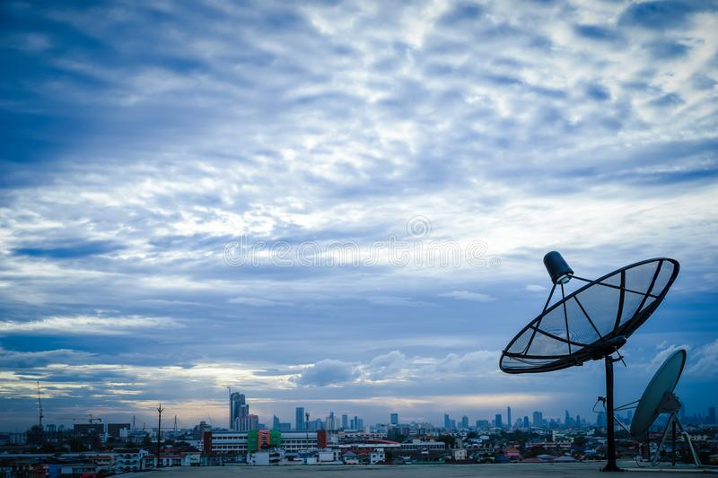 Satellite dish antenna on top of the building in urban area stock photos