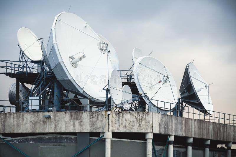 Satellite dish antennas mounted on the roof. Of an industrial building stock photography