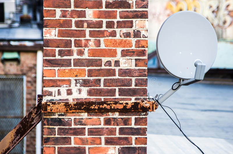 Satellite dish on brick chimney. A satellite dish mounted on a brick royalty free stock photography