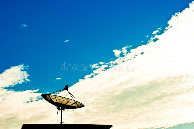 Satellite dish with cloud and sky. A black satellite dish with cloud and blue sky background royalty free stock image