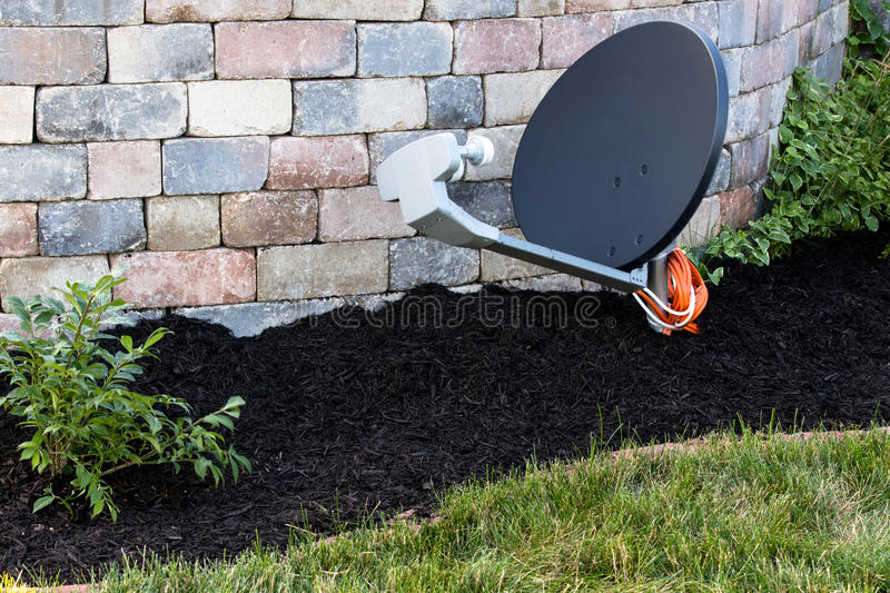 Satellite Dish Ground Mount. Satelleite dish mounted on the ground, hidden next to brick walls on mulch and newly planted bushes royalty free stock photography