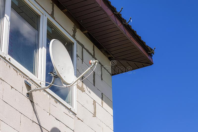 Satellite dish hanging on the wall of the house stock image