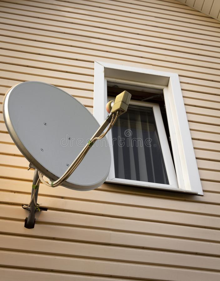 Satellite dish on the house. Satellite dish on the wall of a private house royalty free stock image