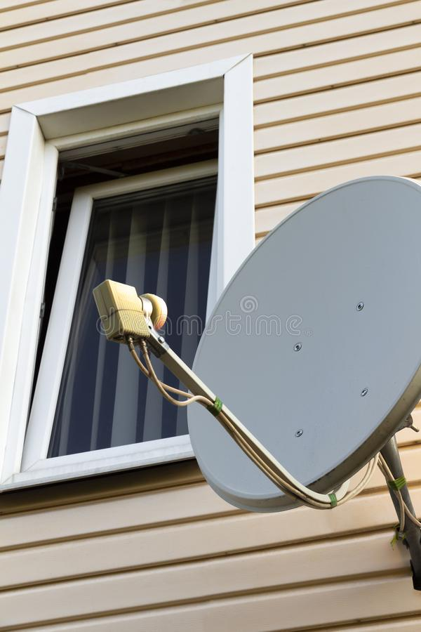 Satellite dish on the house. Satellite dish on the wall of a private house stock image