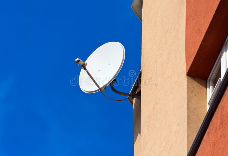 Satellite Dish mounted on brick wall. Against blue sky background royalty free stock image