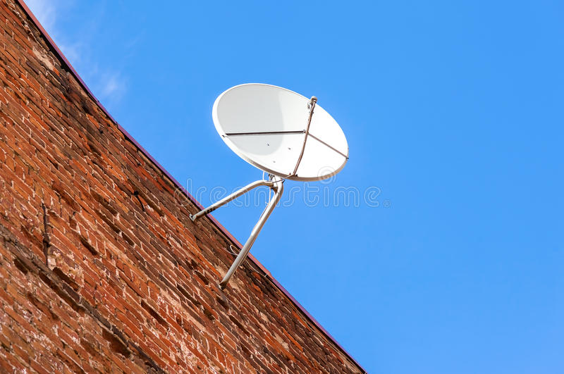 Satellite dish mounted on the grunge brick wall. Of house stock photo