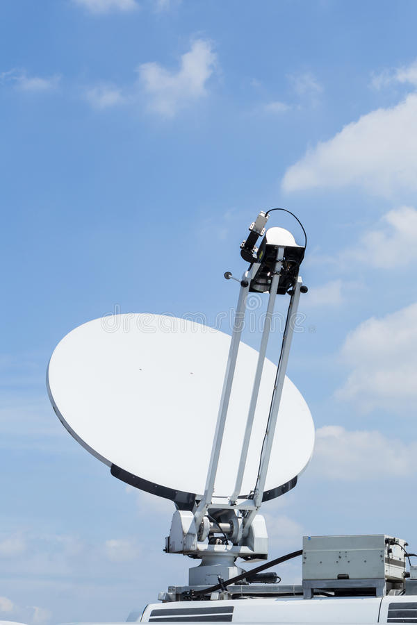 Satellite dish mounted mobile vehicle. Satellite dish mounted mobile vehicle against blue cloud sky royalty free stock images