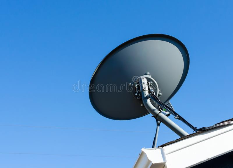 Satellite dish mounted to residential rooftop. With blue sky backdrop. Satellite reception for at home entertainment stock image