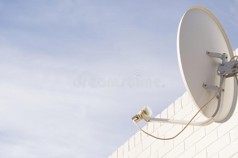 Satellite Dish. Mounted to a white wall of a house against clouds and sky stock image
