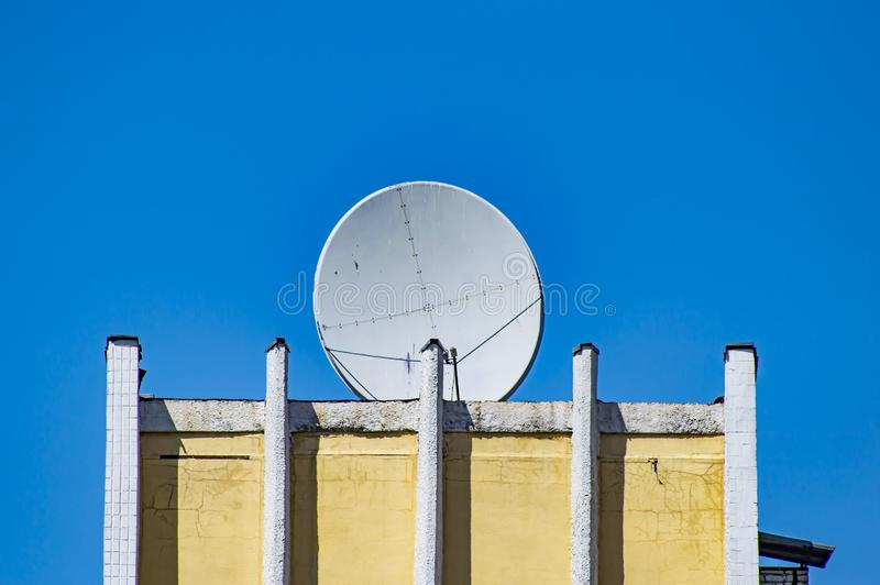 Satellite dish on the roof of the building. Technology royalty free stock photo