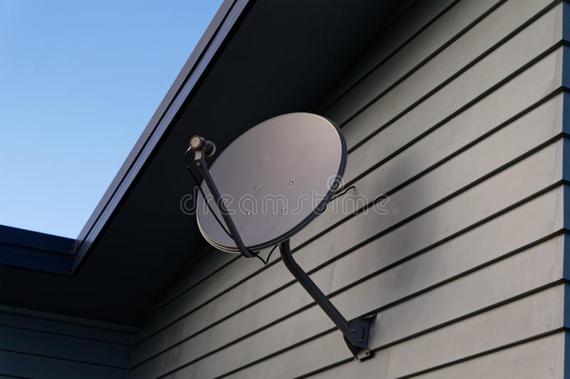 A satellite dish on the side of a building. A grey parabolic dish on the side of a weatherboard house stock images