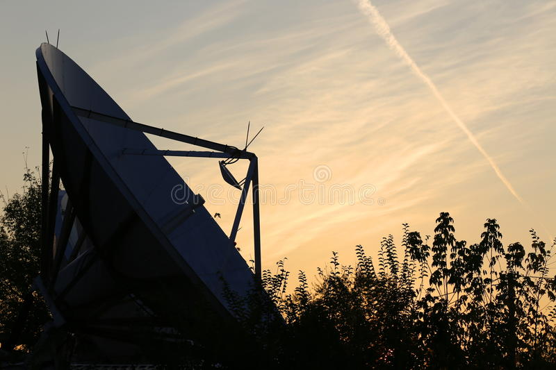 Satellite dish. Sign in the sky left by the passage of an airplane royalty free stock image