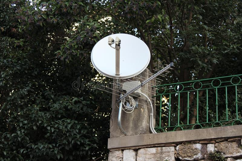 Satellite dish and TV antenna mounted on strong metal pole and concrete fence foundation on top of stone wall with dense tree. Branches and leaves in background royalty free stock images