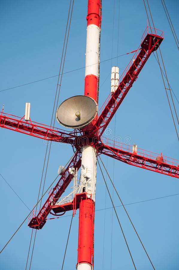 Satellite dishes and antennas on the red-white telecommunication tower against blue sky royalty free stock images