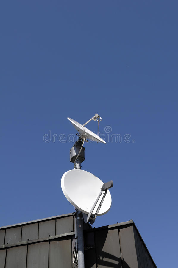 Satellite dishes on rooftop royalty free stock image