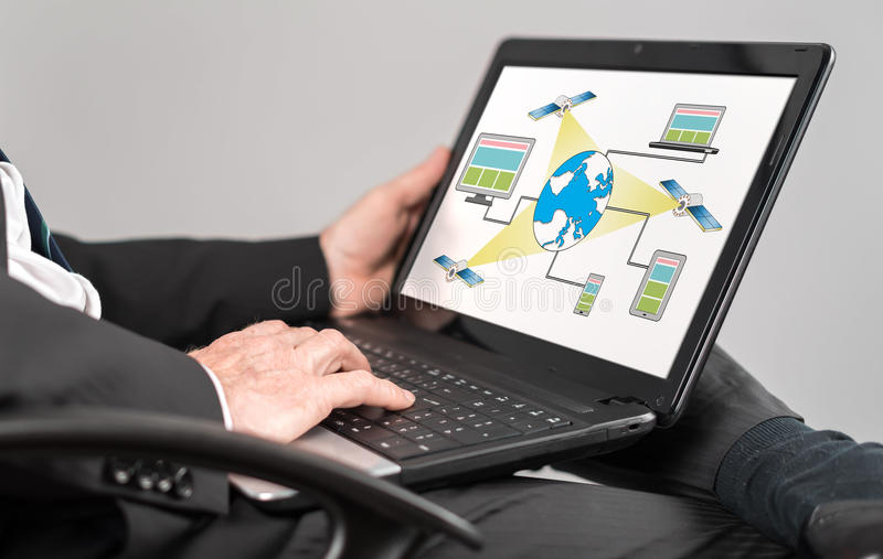 Satellite network concept on a laptop. Businessman watching satellite network concept on a laptop royalty free stock photo