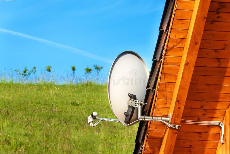 Satellitenfernsehenantenne auf einem Holzhaus Fernsehsignal?bertragung Internet-Zugang Telekommunikation bedeutet stockbild
