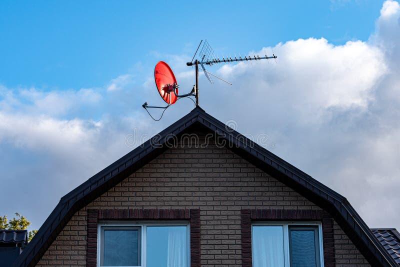 Satellitenschüssel auf dem Dach eines Landhauses gegen den blauen Himmel und die weißen Wolken stockfotografie