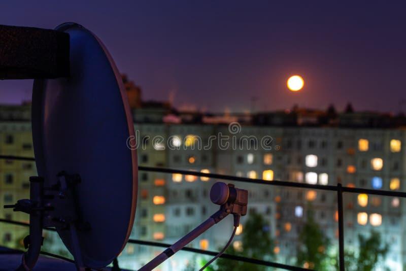 Satellitenschüssel auf russischem Kondominiumdach nachts Vollmond mit selektivem Fokus und Unschärfe stockbild