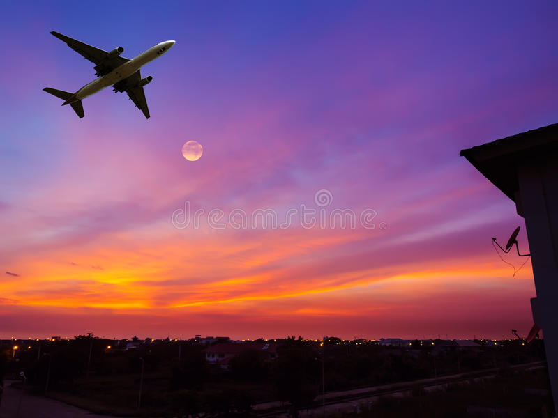 Satellitenschüssel mit Flugzeug und Mond im Sonnenunterganghimmel stockfoto
