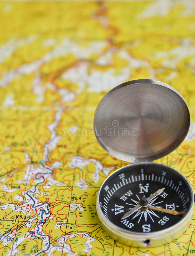 Satellites adventure - map and compass. The magnetic compass is located on a topographic map. Satellites adventure - map and compass royalty free stock photos