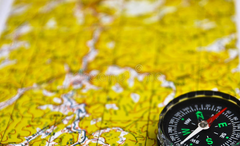 Satellites adventure - map and compass. The magnetic compass is located on a topographic map. Satellites adventure - map and compass royalty free stock images
