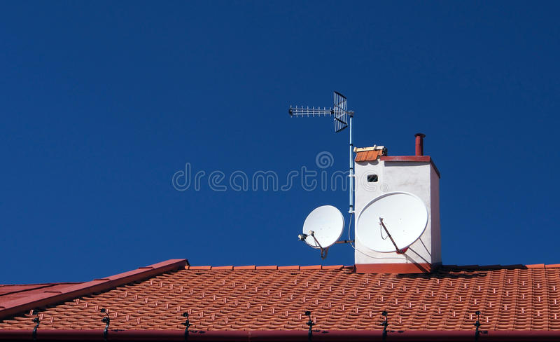 Satellites on roof. Aerial, satellites and chimney on tiled roof with blue sky background royalty free stock photography