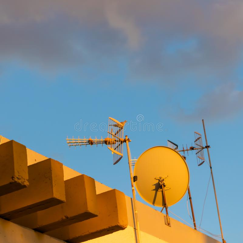 The satellites on the roof of the house with Laughing dove seating on them - Image royalty free stock photos