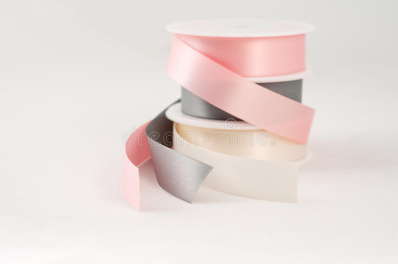 Satin ribbon reels isolated pink gray silver gift royalty free stock images
