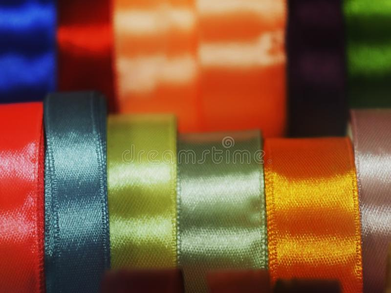 Satin ribbon a substrate background of rainbow colors. Satin ribbon silk different, colors shapes materials blue pink red blue beige background haberdashery stock images