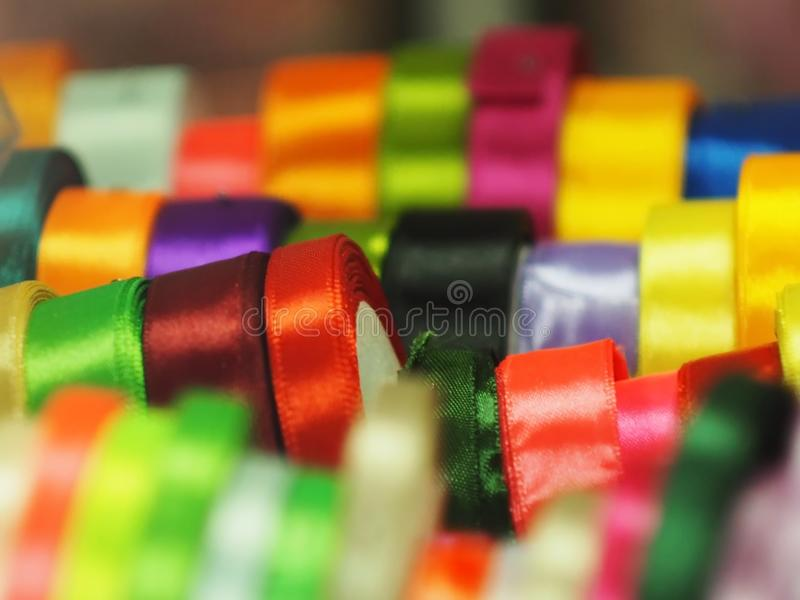 Satin ribbon a substrate background of rainbow colors. Satin ribbon silk different, colors shapes materials blue pink red blue beige background haberdashery royalty free stock photo