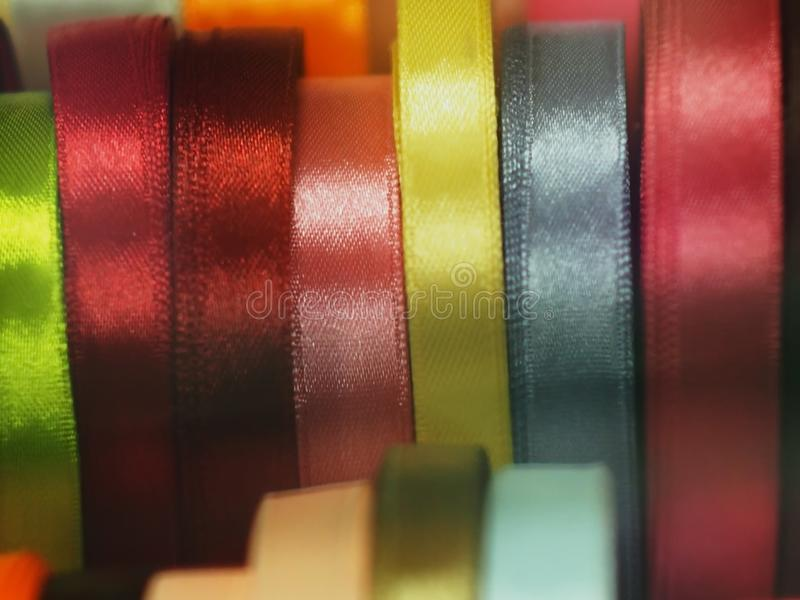 Satin ribbon a substrate background of rainbow colors. Satin ribbon silk different, colors shapes materials blue pink red blue beige background haberdashery stock photos