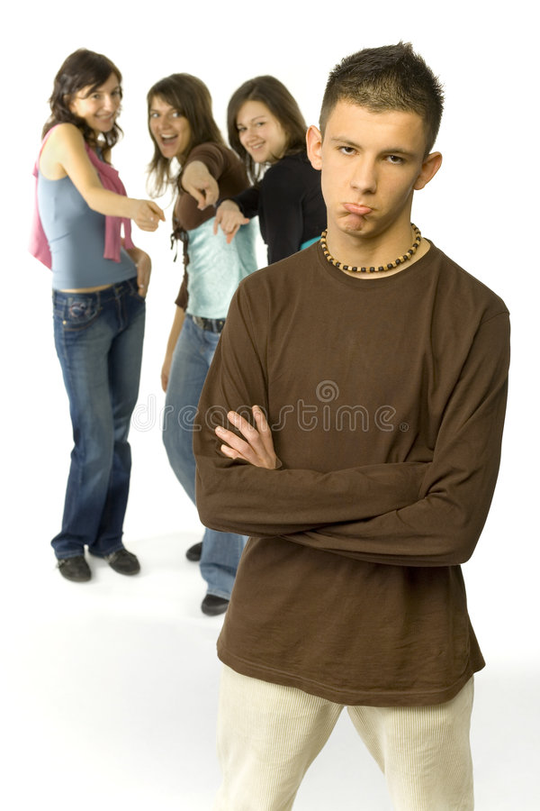Satirizable guy. Sad boy is standing in the foreground. There're 3 mocking girls behind him stock image
