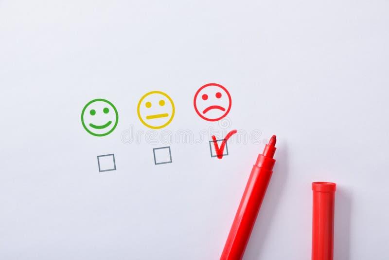 Satisfação negativa com o marcador vermelho representado com os emoticons no papel fotos de stock royalty free