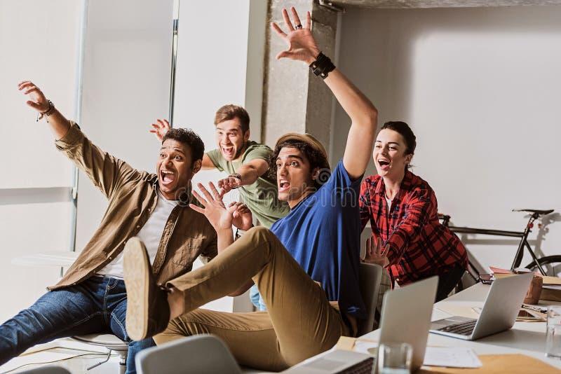 Satisfacen al equipo creativo alegre con su trabajo foto de archivo