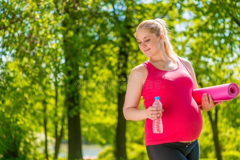 Satisfait avec la femme enceinte tenant un tapis de yoga images stock