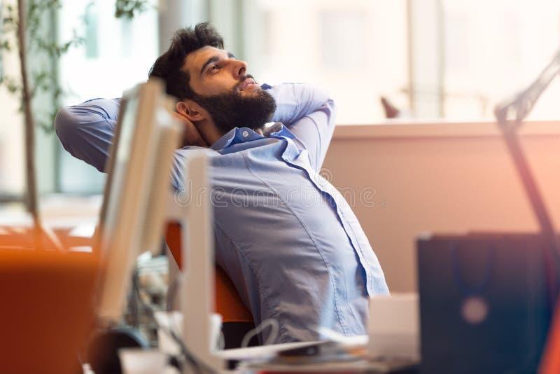 Satisfecho con el trabajo hecho Hombre joven feliz que trabaja en el ordenador portátil mientras que se sienta fotografía de archivo libre de regalías