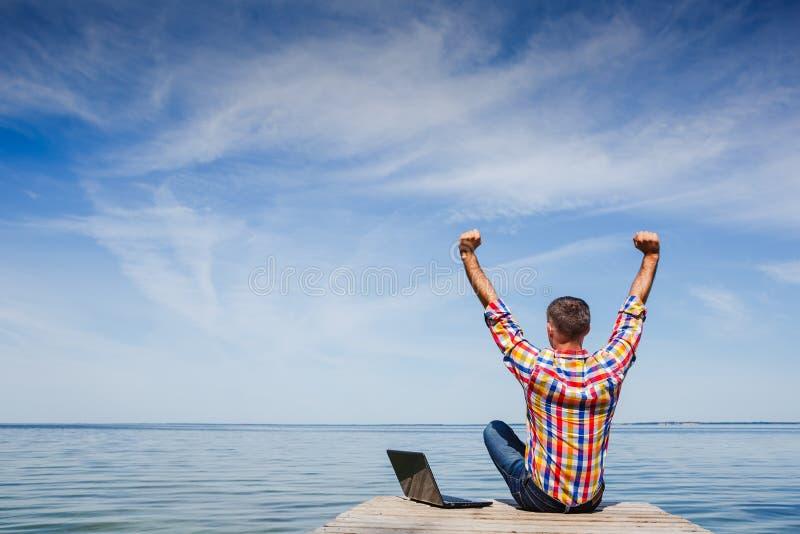 Satisfecho con el trabajo hecho Hombre joven feliz que trabaja en la computadora portátil fotos de archivo