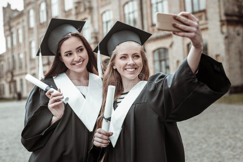 Satisfecho dos hembras que hacen la foto del selfie junto foto de archivo libre de regalías
