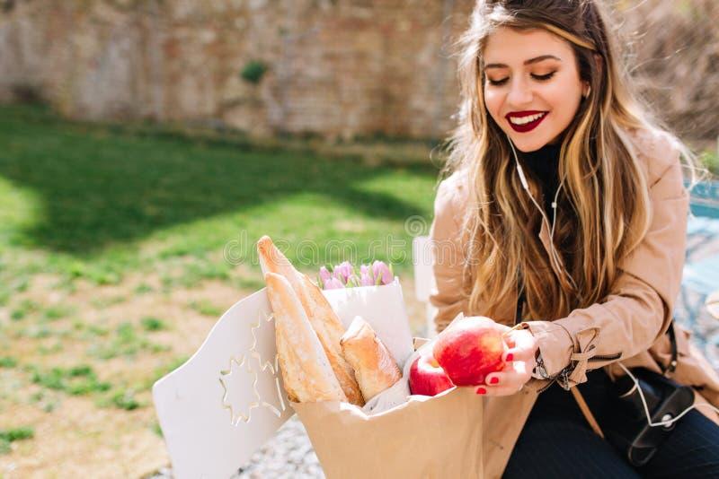 Satisfeito com a menina de compra com o sorriso grande que vê suas compras Alimento de riso e de dobramento da jovem mulher atrat imagem de stock royalty free