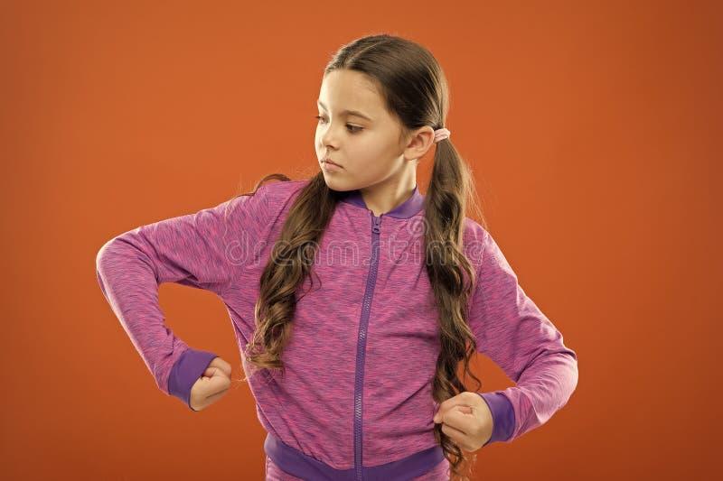Satisfeito com seu corpo forte e saudável Sensação forte Menina bonitinha mostra poder e força dos bíceps Regras para raparigas fotografia de stock