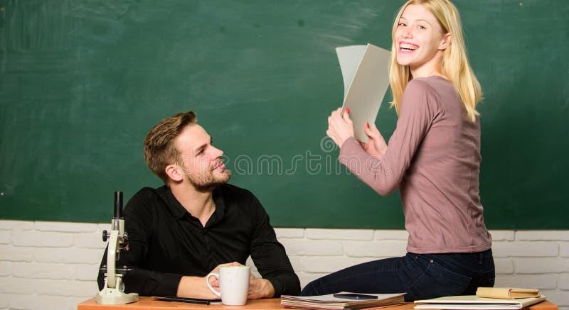 Satisfeito com suas marcas Pares que estudam na sala de aula Papéis de classificação do professor bonito e do professor primário  fotografia de stock