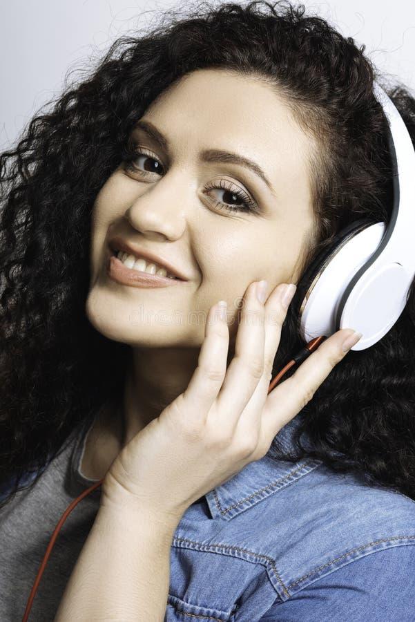 Satisficed que olha a menina que corrige fones de ouvido imagem de stock