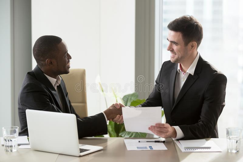 Smiling multinational entrepreneurs shaking hands. Satisfied african american businessman shaking hand to his smiling caucasian partner after singing contract at royalty free stock images