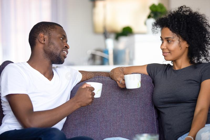 Satisfied African American couple talking, drinking coffee at home royalty free stock image